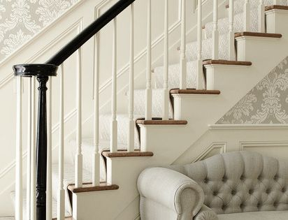 Elegant foyer with silver gray damask wallpaper, wainscoted staircase, glossy black banister
