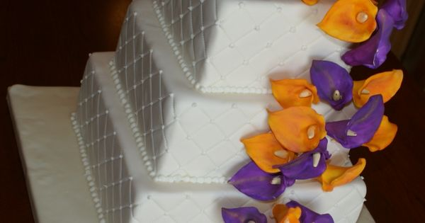 Purple and orange calla lilies on a traditional white wedding cake.