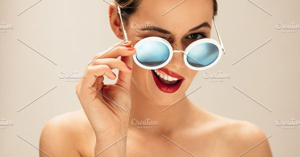 Portrait of beautiful young woman with sunglasses. Female fashion model winking with glasses against beige background.