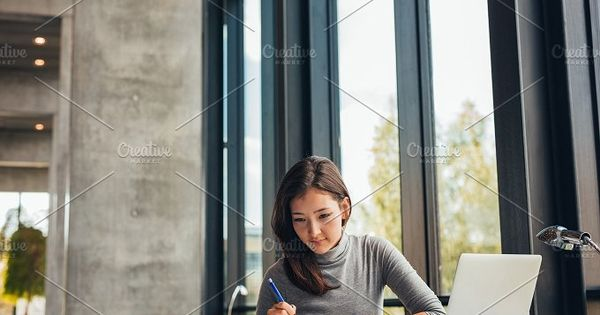 Young asian woman sitting at table with books and laptop for finding information. Young female student studying in library.