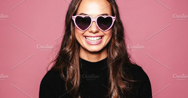 Portrait of beautiful young woman with heart shaped sunglasses and smiling against pink background. Caucasian fashion model posing with glasses.