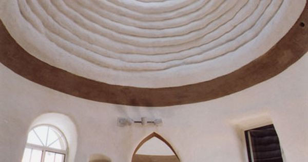 interior of eco dome sandbag house. love the adobe stucco look.