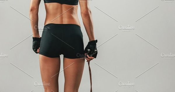 Fit healthy young athlete with a skipping rope standing in black sportswear with her back to the camera looking to the side