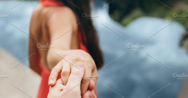 POV shot of man holding hand of his girlfriend. Woman leading man to the pool.