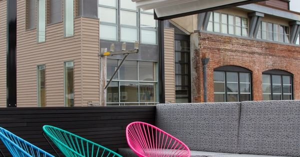 Day Glo Acapulco chairs on urban rooftop space with fire pit