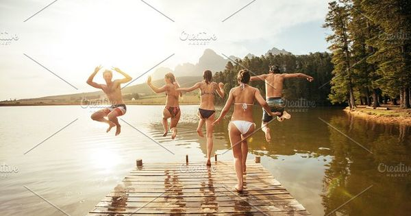 Rear view portrait of young friends jumping into a lake. Young people running and jumping from a jetty in to a lake on a sunny day.