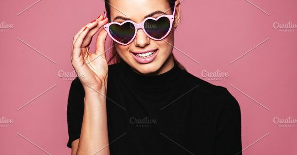 Portrait of pretty young female with heart shaped sunglasses. Caucasian woman posing with glasses against pink background.
