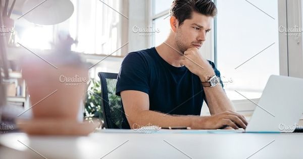 Handsome young man using laptop. Businessman browsing internet on his laptop.