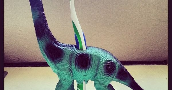 Drill thru dinosaur toy for toothbrush holder