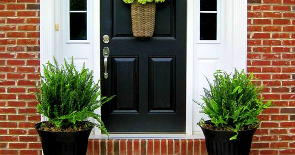 Black front door with potted plants.