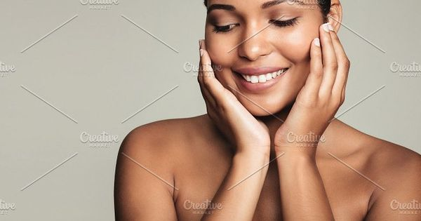 smiling young woman with clean and healthy skin on grey background