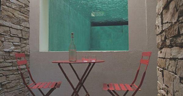 une petite terrasse se trouve en contrebas de la maison l 39 un des c t s de la piscine quip d. Black Bedroom Furniture Sets. Home Design Ideas