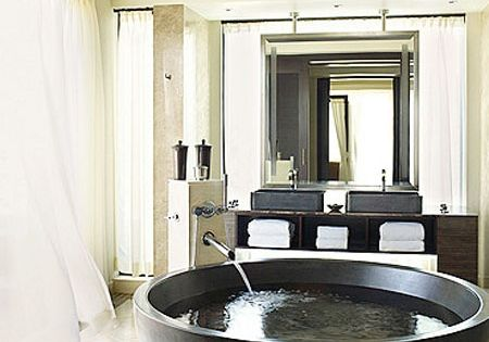 """Black and white bathroom with a large Jacuzzi bathtub, a rain shower,"