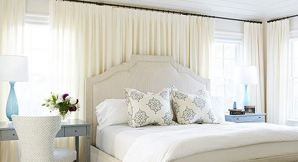 Ivory and gray bedroom features an ivory bed dressed in white and ...