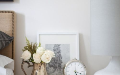 Vignette: fresh flowers, an alarm clock, books & lighting