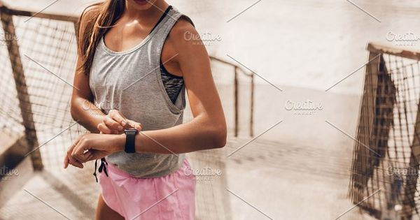 Young woman setting fitness app before workout. Female runner using smart watch to monitor her performance.