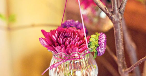"Small glass vases of flowers hung from the branches of a ""wishing"