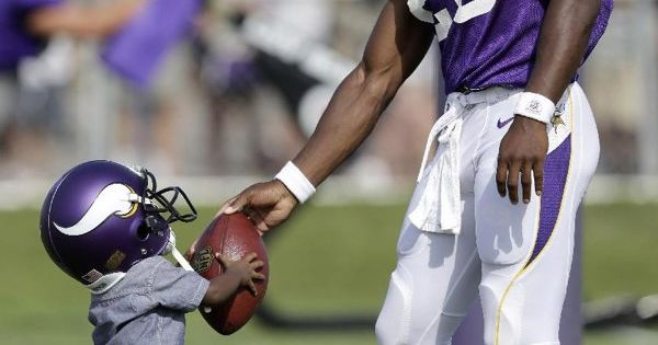 Minnesota Vikings running back Adrian Peterson hands a football to his son