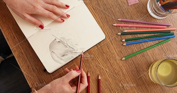Top view of female artist sketching a flower on sketchbook. Woman hands making a flower sketch.