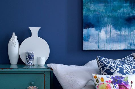 love the floral pop on the pillow in this blue room