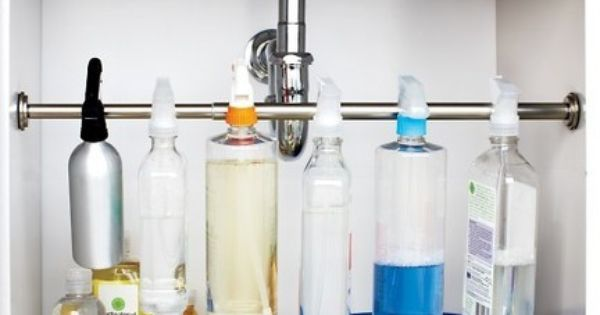 Organize under the kitchen sink by hanging spray bottles across a curtain