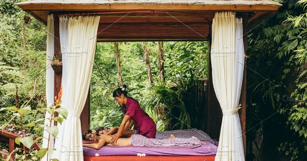 Shot of young man and woman receiving massage at health spa in luxury resort. Couple at outdoor spa center and having body massage. Outdoor spa center at luxury resort.
