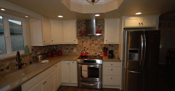Starmark buttercream cabinets with zodiaq mossy green for Chocolate kitchen cabinets with stainless steel appliances