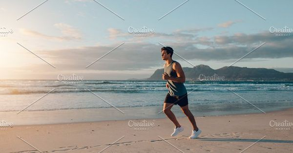 Fit young man jogging on the beach. Healthy male running working out in morning along the sea shore.
