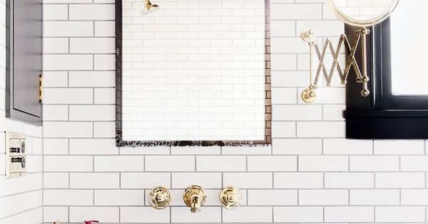Subway tile in black and white bathroom with industrial lighting and gold