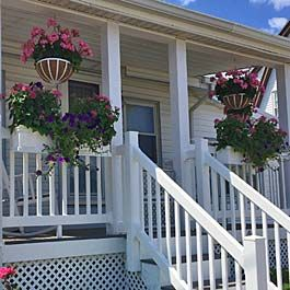 Rail Planters And Hanging Baskets On White Porch Hanging Flower Baskets Flower Window Window Baskets