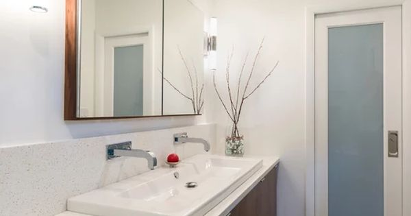 A Custom Walnut Vanity With Washbasin And Chipped Ice Quartz