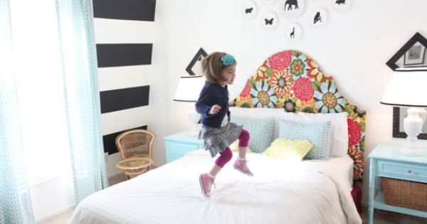 great kids room: colorful upholstered headboard, striped wall