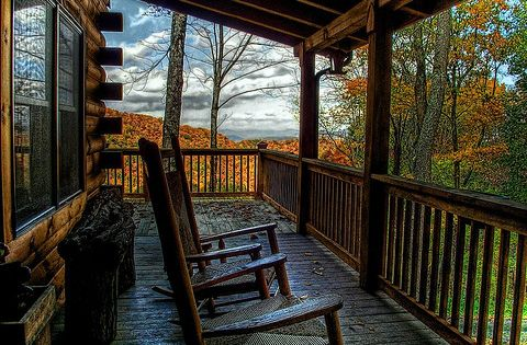 A Rocking Chair On A Log Cabin Porch With A Magnificent