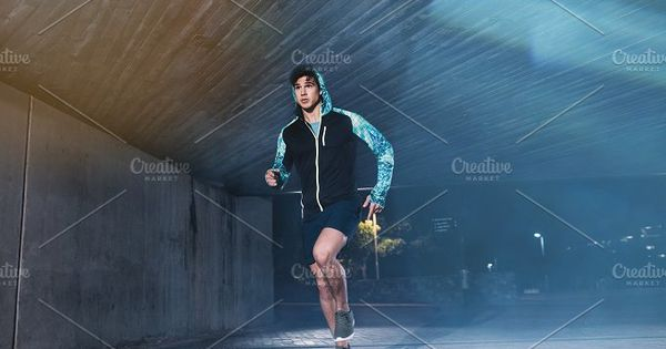 Full length shot of young athlete running under bridge in city. Fit young man jogging in the city.