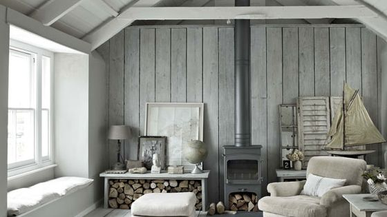 Wood stove, white wood walls and exposed beams. Cabin decor.