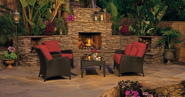 Stone Outdoor Fireplace With Tropical Landscaping And