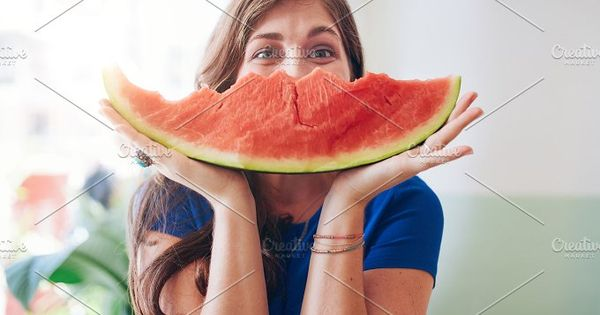 Portrait of young woman holding a slice of watermelon in front of her face.