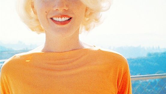 Marilyn Monroe is bright beautiful in a cowl neck orange top.