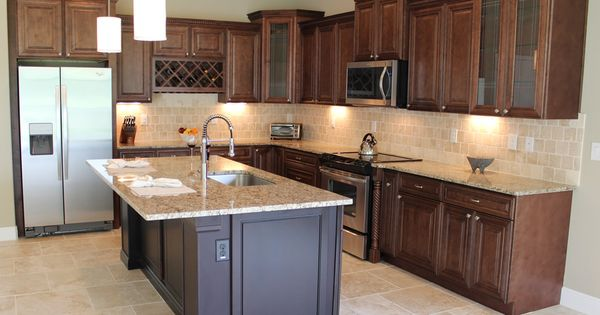 Warm wood stained wall cabinets with a tumbled stone back for Chocolate kitchen cabinets with stainless steel appliances