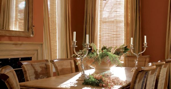 Neutral linen curtains hang in a burnt orange dining room for Burnt orange dining room