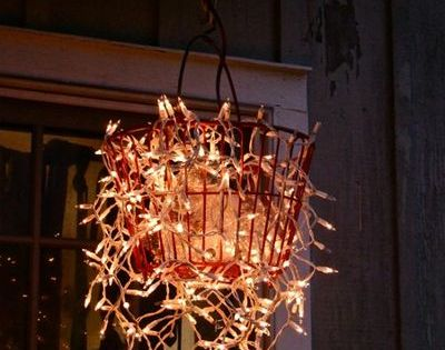use an old egg basket filled with Christmas lights for garden chandelier