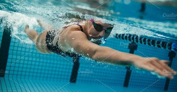 Underwater shot of young sportswoman swimming in pool. Female swimmer inside swimming pool.
