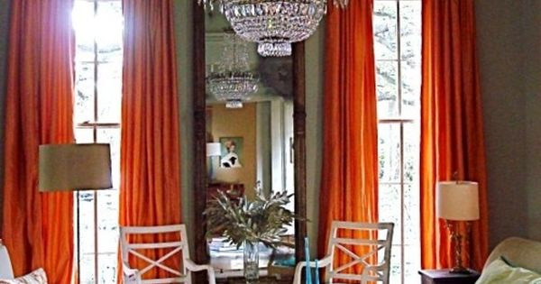 Very tall windows, orange curtains, long mirror, crystal chandelier, large tufted ottoman,