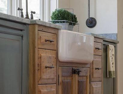 A white apron sink set into a weathered wood base is given