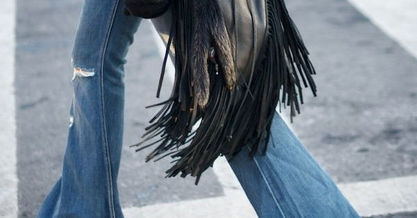 fringed leather bag and bell bottom jeans.