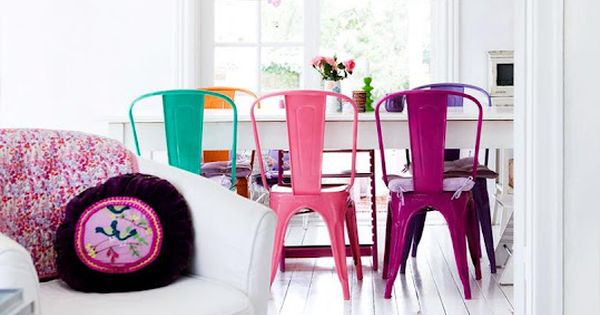 Cute multi coloured dining chairs in very white room