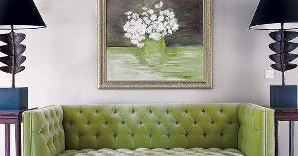Spring green tufted sofa matches still life painting and mid-century modern lamps.