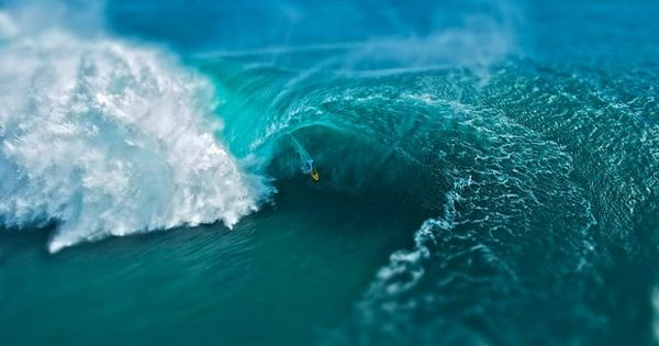 tilt shift photo of big wave surfer