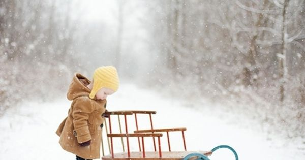 Little girl with sled in snow.