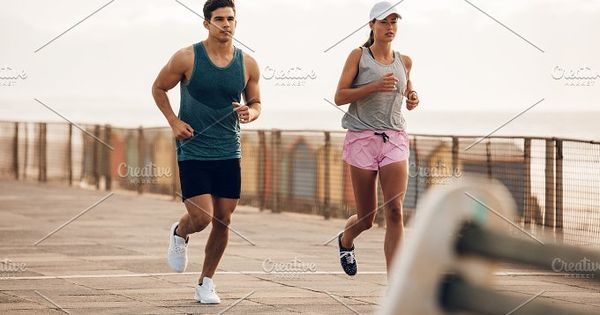 Two runners running along the road by the sea. Fitness couple jogging on the sea side promenade.